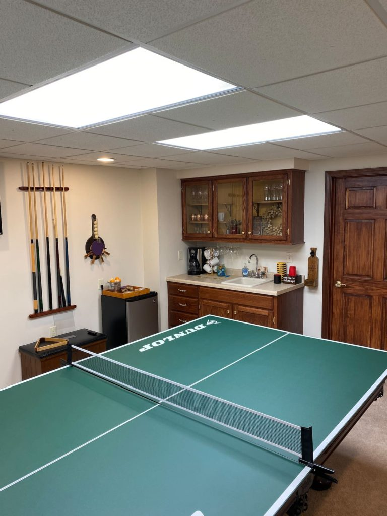 Lower level recreational area with pool table, ping pong overlay and wall mounted flat screen smart tv.