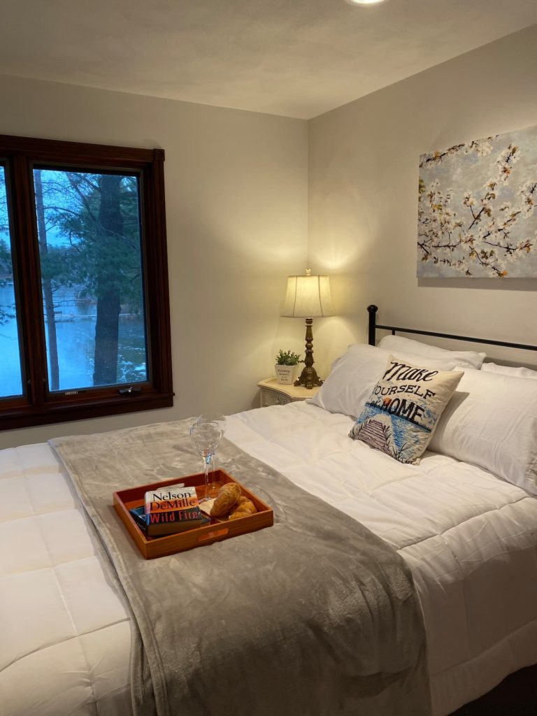 Upper bedroom #1 with lake view. Queen size bed, luggage rack, closet, nightstand, lamp, charging station.