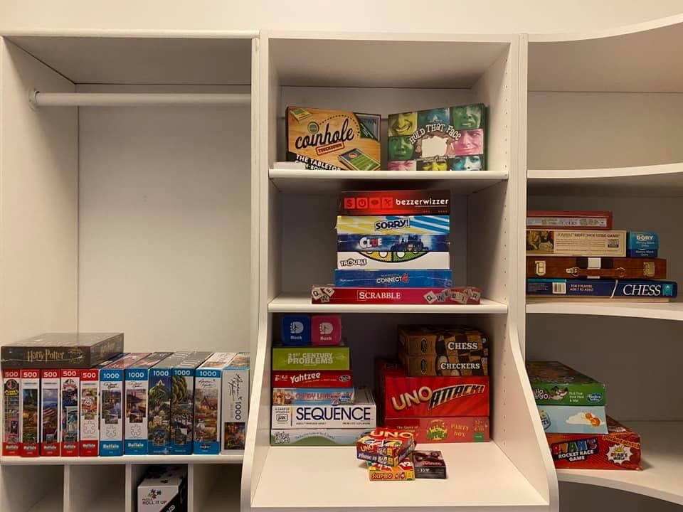 Game closet with board games, puzzles, and card games.