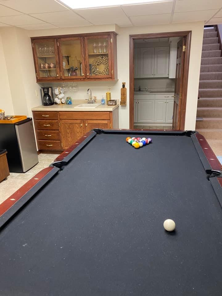 Lower level game area with pool table with ping pong overlay and flat-screen smart tv.