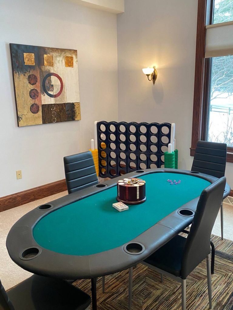 Main level game room with poker table, flat screen Smart tv, blu-ray DVD player, assorted DVDs.